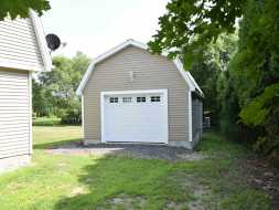 Custom 1 Car Garage with vinyl siding, gambrel roof, a garage bay door, and electrical!