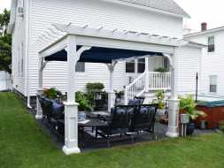 Custom vinyl pergola with superior posts and a shade canopy over an organized outdoor seating area.