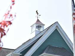 Large custom cupola with arched windows, copper roof, and an eagle weathervane.