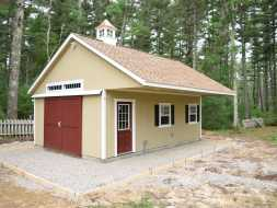 Custom outdoor storage shed featuring duratemp exterior siding, a sliding double barn door, transom windows, roof overhang, and a vinyl cupola!